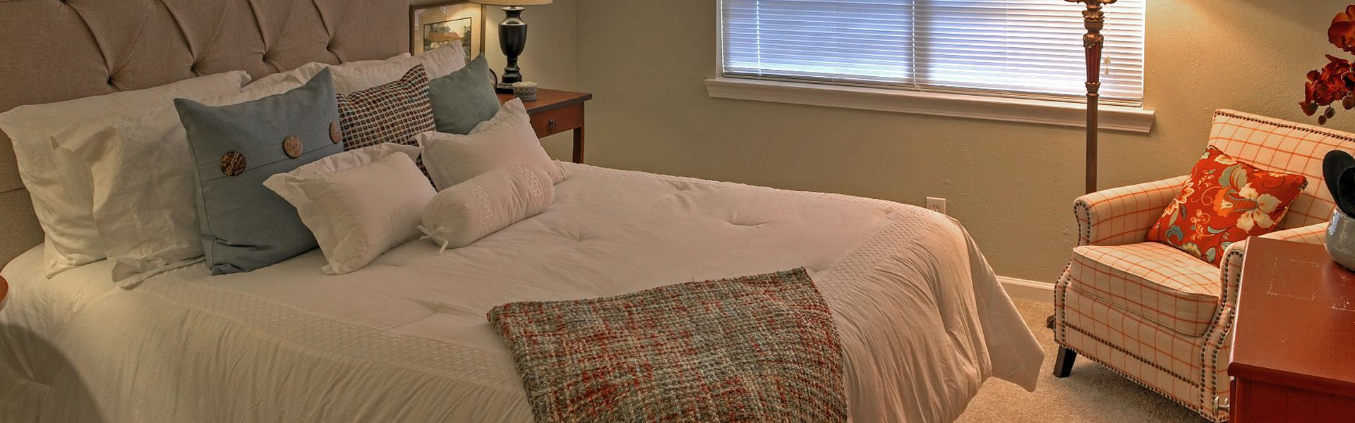 Westside Commons interior apartment. Spacious room with queen bed and night table